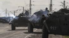 Ukrainian armored personnel carriers are seen near the village of Salkovo, in Kherson region adjacent to Crimea, March 18, 2014. (VALENTYN OGIRENKO/REUTERS)