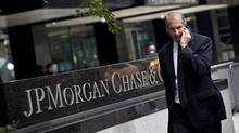 A pedestrian passes JP Morgan Chase & Co.'s international headquarters in New York. The bank is one of five providing mortgage relief to customers under a deal to settle borrowers' accusations over foreclosures. (ANDREW BURTON/REUTERS)