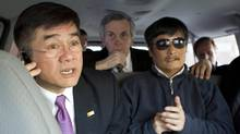 In this photo released by the US Embassy Beijing Press Office, U.S. ambassador to China, Gary Locke, left, makes a phone call as he accompanies blind lawyer Chen Guangcheng, right, in a car en route from the U.S. Embassy to a hospital in Beijing, Wednesday, May 2, 2012. At center is language attache James Brown. (Uncredited/AP)
