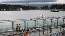A Harbour Air float plane, centre, taxis on Burrard Inlet as workers look out from a new float plane terminal under construction in Vancouver, B.C., on Wednesday January 19, 2011. Float plane operators are embroiled in a dispute with the developers of the new $22 million facility scheduled to open in May over a $12 one-way fee for passengers departing from and arriving at the new terminal. (Darryl Dyck/The Canadian Press/Darryl Dyck/The Canadian Press)
