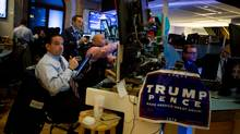 A campaign sign for U.S. President-elect Donald Trump and U.S. Vice President-elect Mike Pence hangs on a desk while traders work before the opening bell of the New York Stock Exchange (NYSE) on Wednesday, Nov. 9. (Michael Nagle/Bloomberg)