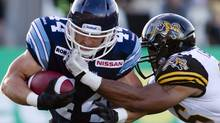 Toronto Argonauts' Chad Kackert, left, is tackled by Hamilton Tiger-Cats' Ike Brown during first half CFL pre-season action in Hamilton on June 13, 2013. (The Canadian Press)