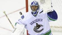 Vancouver Canucks goaltender Roberto Luongo prepares to glove the puck during the third period of an NHL game against the New Jersey Devils, Thursday, Oct. 24, 2013, in Newark, N.J. (Bill Kostroun/AP)