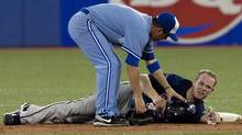 Toronto Blue Jays' John McDonald,left, checks on Minnesota Twins Justin Morneau after the pair collided at second base after Twins' Michael Cuddyear grounded into fielders choice during eighth inning baseball action in Toronto Wednesday, July 7, 2010. (Chris Young/The Canadian Press)