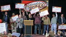 In this Feb. 22, 2006, file photo, the eight winners of the $365-million Nebraska Powerball lottery hold up their ceremonial checks at a news conference in Lincoln, Neb. As the drawing for a $500 million Powerball jackpot approaches, Wednesday, Nov. 28, 2012, past winners of mega-lottery drawings and financial planners have some advice: stick to a budget, invest wisely, learn to say no and be prepared to lose friends while riding an emotional roller-coaster. (Nati Harnik/AP)