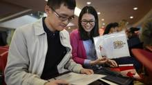 Furong Liu, left, and his sister Liwen, who both live in Markham, Ont., look over the citizenship certificates they received during a citizenship ceremony at Seneca College in Markham on Oct. 23. 2013. (Fred Lum/The Globe and Mail)