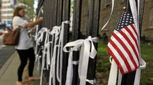 """woman ties a """"Ribbon of Remembrance"""" onto the fence at St. Paul's Chapel on September 8, 2011 in New York City. (Tama/Getty Images)"""
