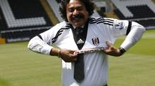 "The new owner of Fulham Football Club, Shahid Khan, tries on a team shirt as he poses for photographers at the club's Craven Cottage ground, in west London July 13, 2013. Mohamed Al Fayed, the man behind Fulham's modern rebirth, has asked the fans to get behind new owner Shahid Khan while describing Friday's takeover as a ""new era"" for the club. (LUKE MACGREGOR/REUTERS)"