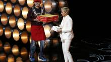 Show host Ellen DeGeneres receives pizza to be given to the audience at the 86th Academy Awards in Hollywood, California March 2, 2014 (LUCY NICHOLSON/REUTERS)