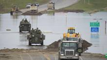 Military personnel drive in a light-armoured vehicle across a washed-out highway to High River on June 24, 2013. (JOHN LEHMANN/THE GLOBE AND MAIL)