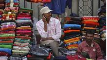 A vendor speaks on his mobile phone as he waits for customers at his roadside shop selling clothes in Mumbai February 2, 2012. (DANISH SIDDIQUI/REUTERS/Danish Siddiqui)