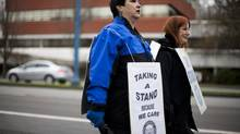 Louella Vincent (left) and Sue Munn of the Hospital Employees' Union walk in solidarity with other community living workers from various unions that include CUPE, BCGEU and HEU outside the Richmond Caring Place in Richmond, B.C. (Rafal Gerszak For The Globe and Mail)