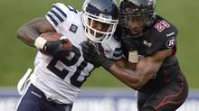Toronto Argonauts' Steve Slaton (20) keeps Ottawa Redblacks' Seth Williams (23) away from the ball during first half CFL action in Ottawa on Friday, July 18, 2014. (Justin Tang/THE CANADIAN PRESS)