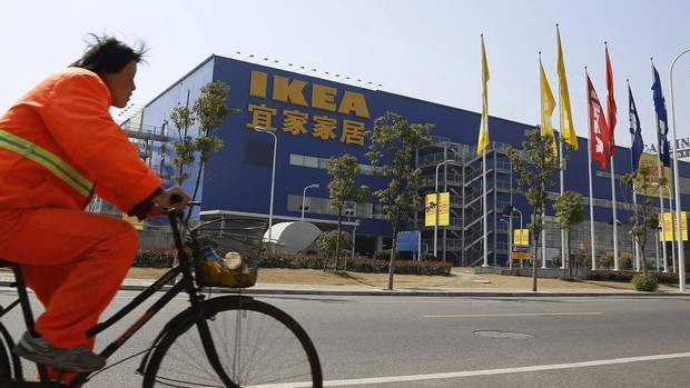 A public worker rides a bicycle in front of an IKEA store March 6, 2013 in Shanghai. The company has 11 stores in China with plans to triple that number. (STR/AP)