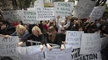 Demonstrators wave banners and shout slogans during a protest outside the Cypriot parliament in Nicosia on Friday. (Simon Dawson/Bloomberg)