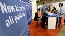 Exhibitors speak with visitors at a job fair in Toronto in this file photo. (AARON HARRIS/REUTERS)