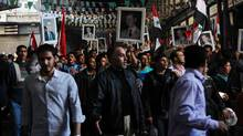 Syrian pro-government protesters hold pictures of Syrian President Bashar al-Assad and his late father and predecessor Hafez al-Assad, left, during a pro-regime rally at Al-Hamidiyah market in Damascus on March 18, 2011. (-/AFP/Getty Images)