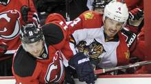 New Jersey Devils Stephen Gionta, left, checks Florida Panthers Keaton Ellerby into the boards during the second period of Game 4 of their NHL Eastern Conference quarter final playoff hockey game in Newark, New Jersey, April 19, 2012. (Reuters)