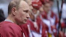 Russian President Vladimir Putin takes a break during a friendly hockey match at The Bolshoy Ice Dome, the part of the complex of facilities operated by the International Ice Hockey Federation (IIHF) at the Black Sea resort of Sochi, southern Russia, Jan. 4, 2014. (Alexei Nikolsky/AP)