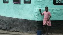 A young girl stands along a street in Ghana before a 2009 visit by U.S. President Barack Obama. Accusations of witchcraft are a disturbing example of a lesser-known form of violence to which women can be subjected daily in some areas of the world. (REBECCA BLACKWELL/Associated Press)