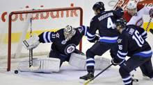 Winnipeg Jets goaltender Ondrej Pavelec makes a save on Montreal Canadiens' Andrei Kostitsyn (46) as Jets' Zach Bogosian (4) and Andrew Ladd (16) watch the rebound during the second period of their NHL hockey game in Winnipeg December 22, 2011. (FRED GREENSLADE/REUTERS)