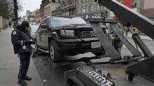 A Toronto Parking enforcement officer beside a vehicle being towed after parking illegally during rush hour on Church St., Toronto January 04, 2012. (Fernando Morales/The Globe and Mail)