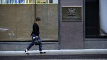 Pedestrians walk past the Hudson's Bay Company store at Queen St. West and Yonge St. in Toronto. (Fred Lum/The Globe and Mail)