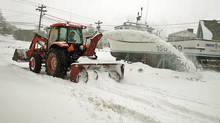 Ronald Toombs clears snow in North Rustico, PEI, on Feb. 16, 2014. A major winter storm has battered the Maritimes with high winds, blowing snow and storm surges along the coast. (ANDREW VAUGHAN/THE CANADIAN PRESS)