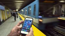 A commuter looks at his smart phone on the Metro, Wednesday, September 25, 2013 in Montreal. Telus Rogers and Quebecor have announced plans to build a wireless network in the subway that will allow riders to use their phone, laptops and tablets underground. (Ryan Remiorz/THE CANADIAN PRESS)