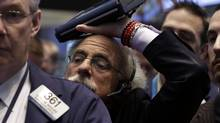 Trader Peter Tuchman rests his handheld device on his head as he works on the floor of the New York Stock Exchange Friday, Jan. 31, 2014. (Richard Drew/AP)