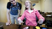 Corinne Eisenstein,17, who has cerebral palsy and is a quadriplegic, listens to her ipod music player through mini speakers as Carl Spani, the designer of the CanPlay podWiz device by CanAssist , watches over her shoulder, at the University of Victoria Thursday. (Deddeda Stemler)