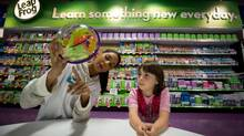 Toys R Us Wonderlab salesperson Chyanne Sharma, left, demonstrates how to solve a Perplexus puzzle game for Kayla Henry, 7, at the new store in North Vancouver, B.C., on May 23, 2013. (DARRYL DYCK FOR THE GLOBE AND MAIL)