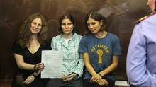 Feminist punk group Pussy Riot members, from left, Maria Alekhina, Yekaterina Samutsevich, and Nadezhda Tolokonnikova show the court's verdict as they sit in a glass cage at a court room in Moscow, Russia on Friday, Aug 17, 2012. A judge found three members of the provocative punk band Pussy Riot guilty of hooliganism on Friday, in a case that has drawn widespread international condemnation as an emblem of Russia's intolerance of dissent. (Mikhail Metzel/AP)