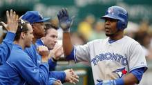 Toronto Blue Jays base runner Edwin Encarnacion (10) is congratulated after scoring a run during the eleventh inning of their MLB game against the Oakland Athletics in Oakland August 4, 2012. (BECK DIEFENBACH/REUTERS)