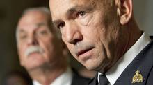 Public Safety Vic Toews looks on as newly appointed RCMP Commissioner Bob Paulson takes question from reporters in the foyer of the House of Commons on Nov. 16, 2011. (Adrian Wyld/Adrian Wyld/The Canadian Press)