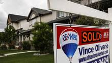 A real estate sign hangs in front of a Calgary, Alta., home in June. (Jeff McIntosh For The Globe and Mail)