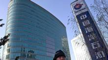 A man walks past the headquarters of the state-owned China National Offshore Oil Corp. in Beijing, China, in 2012. (Andy Wong/AP)