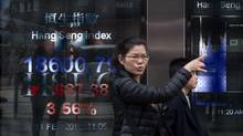 A woman gestures as she walks past a display showing the Hang Sang index outside a bank on the first day of trading of the Lunar New Year in Hong Kong on Feb. 11, 2016. Hong Kong stocks plunged more than 4 per cent. (DALE de la REY/AFP/Getty Images)