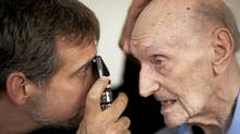 Dr. Jay Slater (L) on one of his house calls looks over patient Hal Rodd at his home in Vancouver October 10, 2010. (JOHN LEHMANN/John Lehmann/The Globe and Mail)