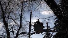 A Toronto Hydro line worker works to restore power to a house in a Scarborough neighbourhood on Friday, December 27, 2013. (Chris Young/THE CANADIAN PRESS)