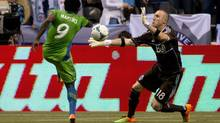 Seattle Sounders' Obafemi Martins, left, of Nigeria, is stopped by Vancouver Whitecaps' goalkeeper Brad Knighton during the first half of an MLS soccer game in Vancouver, B.C., on Saturday July 6, 2013. (DARRYL DYCK/THE CANADIAN PRESS)
