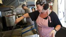 Cooks prepare food at the Rome'n Chariot food truck in Toronto, Ont. on July 4, 2012 (KEVIN VAN PAASSEN/THE GLOBE AND MAIL)