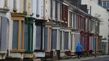 A man walks past a row of boarded up terraced houses in the Kensington area of Liverpool, northern England February 20, 2013. Liverpool city council are planning to sell off up to 20 derelict houses in a failed regeneration area for one GB Pound each, in an attempt to kick start regeneration following the failure of a planned regeneration scheme. (Phil Noble/Reuters)