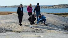 Prime Minister Stephen Harper points to a rock as he is given a geological tour by National Resources Canada Geologist Donna Kirkwood, bottom right, and Denis St-Onge of the Canadian Geological Survey, right, along with wife Laureen Harper, middle, and Minister of Natural Resources Joe Oliver, left, in Rankin Inlet, Nunavut on Thursday, August 22, 2013. (Sean Kilpatrick/THE CANADIAN PRESS)