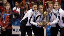 Canada skip Rachel Homan, left, looks on as Switzerland's Binia Feltscher, Irene Schori, Franziska Kaufmann and Christine Urech, left to right, stand on the podium after defeating Canada 9-5 to win the gold medal at the Ford World Women's Curling Championships in Saint John, N.B. on Sunday, March 23, 2014. (Andrew Vaughan/CP)