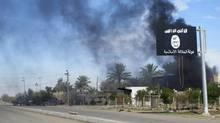 Smoke raises behind an Islamic State flag. (REUTERS)