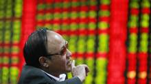 An investor gestures as he looks at an electronic board showing stock information at a brokerage house in Huaibei, Anhui province, October 25, 2012. (Stringer/Reuters)