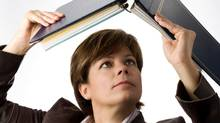 Business woman reading a binder upside down. (Claude Dagenais/Getty Images/iStockphoto)