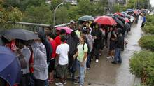 Hundreds of youth wait under the rain while lining up to apply for a job at the CNE job fair Aug. 9, 2011. (Fernando Morales/The Globe and Mail)