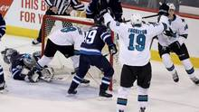 Winnipeg Jets goaltender Connor Hellebuyck lays on the ice as San Jose Sharks' Joe Pavelski ends up in the net after scoring during first period NHL hockey action in Winnipeg, on March 6, 2017. (Trevor Hagan/THE CANADIAN PRESS)